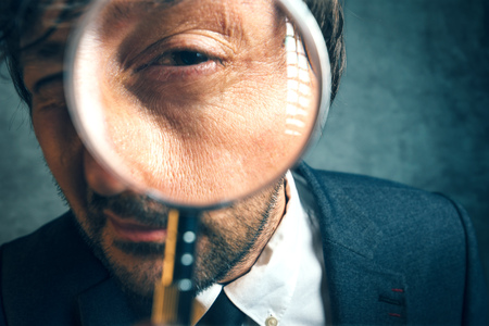 looking glass: Enlarged eye of tax inspector looking through magnifying glass, inspecting offshore company financial papers, documents and reports.