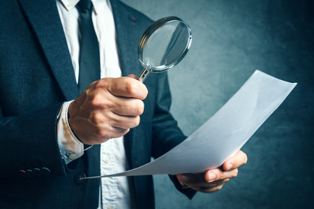 Tax inspector investigating financial documents through magnifying glass, forensic accounting or financial forensics, inspecting offshore company financial papers, documents and reports. Imagens