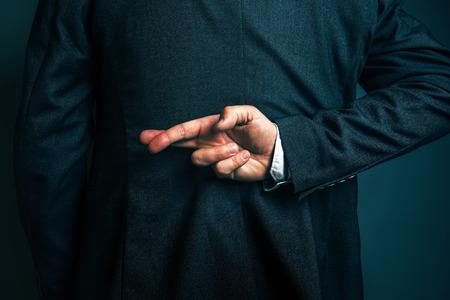 持株指実業家を横になっている、嘘を言って不誠実なビジネスマンが彼の背中の後ろに交差 写真素材