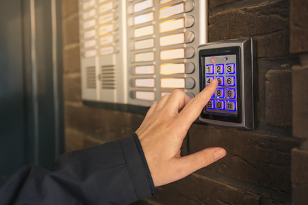 Woman dialing pass code on intercom security keypad to open entrance door of the apartment building.