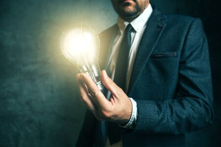 enlightment: Business creativity and vision concept with elegant adult businessman holding bright light bulb as metaphor of new ideas in hand