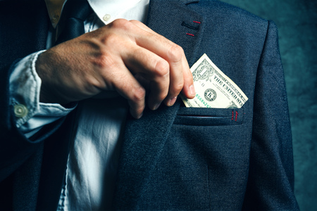 putting money in pocket: Businessman putting dollar banknotes money in his suit pocket, elegant businessperson with cash. Stock Photo