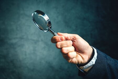business tool: Business analytics and statistics using a magnifying glass, businessman holding vintage tool for optical enlargement Stock Photo