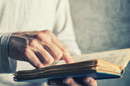 lexicon: Man reading old book with torn pages, close up of adult male hands holding vintage book. Stock Photo