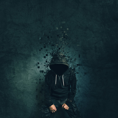 hooded shirt: Spooky evil criminal person with hooded jacket dissolving in front of concrete wall.
