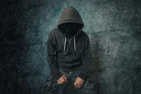 uomo sotto la pioggia: Spooky persona criminale male con giacca con cappuccio in piedi sotto la pioggia di fronte al muro di cemento. Archivio Fotografico