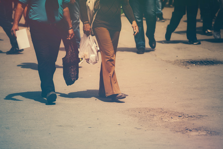 workday: Retro toned image of pedestrians walking the street on a sunny day Stock Photo