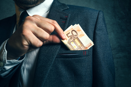 putting money in pocket: Businessman putting euro banknotes money in his suit pocket, elegant businessperson with cash.