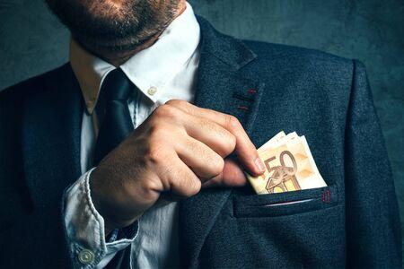 putting money in pocket: Businessman putting cash money in his pocket, elegant businessperson with euro banknotes Stock Photo