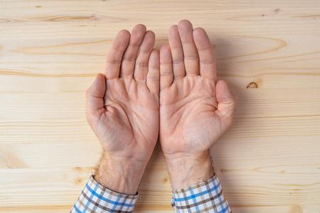 palmeras: Vista superior de las palmas mlae caucásico en el escritorio, concepto de la oración, necesidad o motivo, con las manos vacías pidiendo algo Foto de archivo