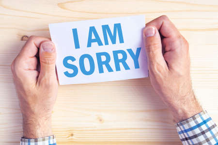 i am sorry: I am sorry message, top view of male hands holding apologizing card