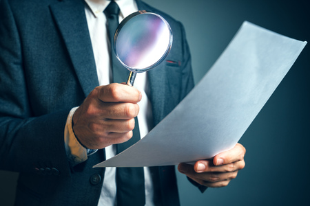 Lawyer reading legal contract agreement disclaimer with magnifying glass, person in elegant business suit reading document. Stock Photo