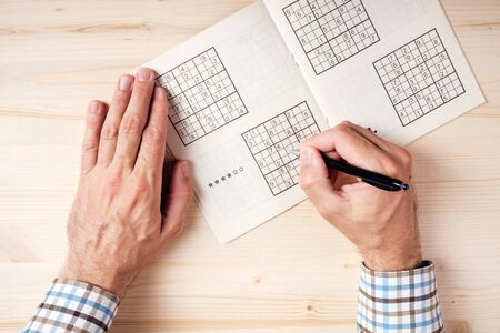 crossword puzzle: Top view of male hands solving sudoku puzzle on wooden office desk