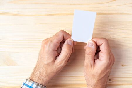 graphic design: Top view of businessman holding blank business card on office desk, mock up copy space for graphic design or text placement.