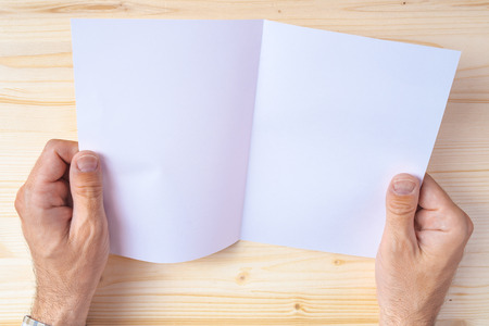 blank newspaper: Man holding blank brochure as mock up copy space for graphic design or text placement