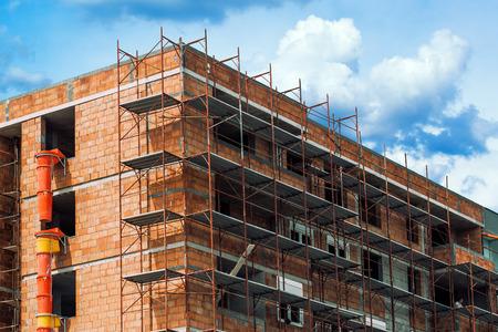 construccion: Andamio alrededor del edificio unrendered y sin revocar en el sitio de construcción del nuevo distrito residencial de apartamentos.