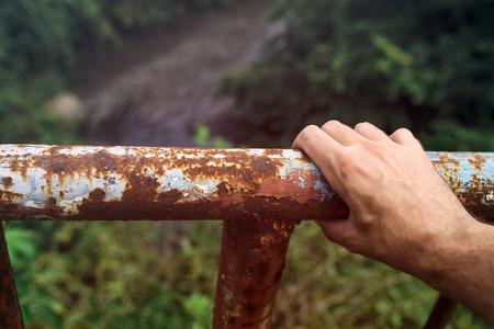 salto de valla: agarre la mano masculina a una valla oxidada puente del r�o, el concepto de tendencias suicidas, saltando por encima del borde.