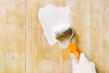 Main Avec Un Rouleau à Peinture à Appliquer La Laque Acrylique Sur Panneau  De Bois,