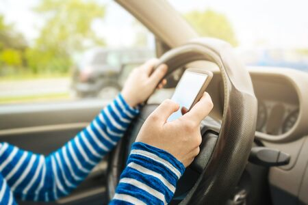 risky behavior: Woman driving car and texting message on smartphone, using mobile phone device while driving, dangerous and risky behavior in traffic