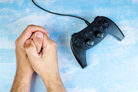 entertainment equipment: Man resisting video game addiction, top view of crossed male hands and gamepad on the desk