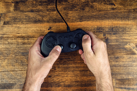 gamepad: Male gamer using gamepad controller on wooden desk, flat lay top view, gaming and entertainment concept