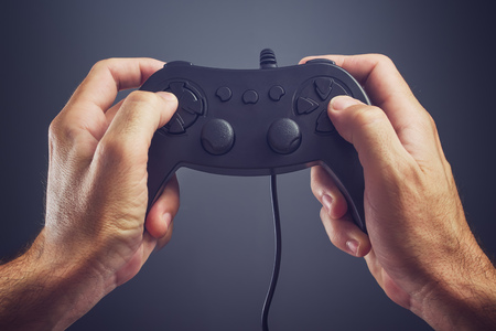 entertaining: Man using game pad controller to play entertaining electronics video games, gaming and entertainment concept