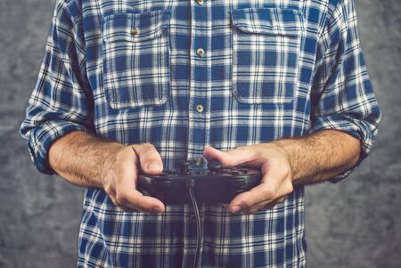 gamer: Gamer in plaid shirt playing video game with gamepad, gaming and entertainment concept Stock Photo