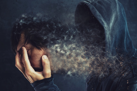 Hooded man taking off his face mask, revealing spooky faceless person behind Stock Photo