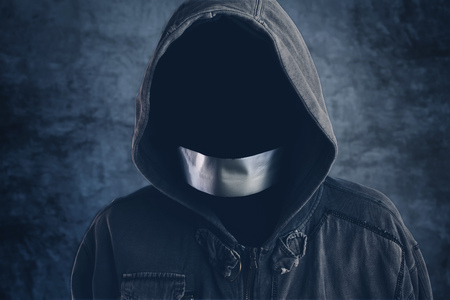 taped: Unrecognizable hooded hooligan with mouth duct taped, spooky faceless criminal person in jacket with hood Stock Photo