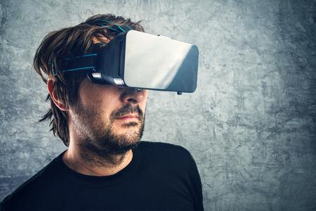 virtual reality simulator: Adult man with 3d VR goggles enjoying virtual reality, modern futuristic technology gadget