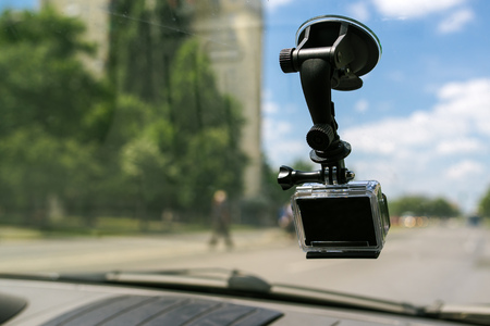 suction: Action camera with suction cap on car windshield window, filming the driving experience in urban traffic environment Stock Photo