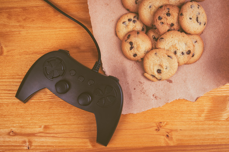 nostalgia: Gamepad and homemade chocolate chip cookies on rustic wooden table, top view, concept of childhood memories and nostalgia.