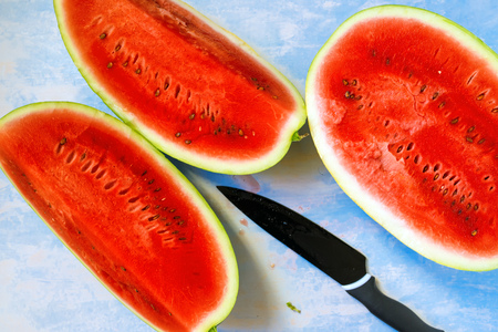 Watermelon slices and cutting knife on rustic blue wooden table as natural summertime background, top view, selective focus Stock Photo