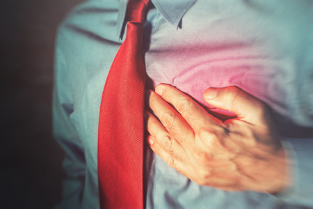 Unrecognizable businessman having chest pain and heart attack, hand holding the painful spot.