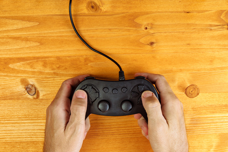 controlling: Man using game pad controller on wooden desk, flat lay top view, gaming and entertainment concept