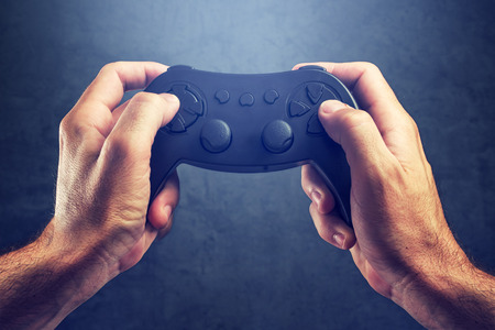 gamer: Man using game pad controller to play entertaining electronics video games, gaming and entertainment concept