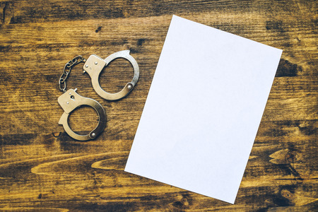 delinquent: Police handcuffs and blank paper on investigator detectives work desk, concept of law and crime.