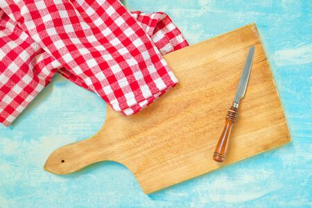 household objects: Rustic kitchen household objects, top view of knife, cutting board and table cloth