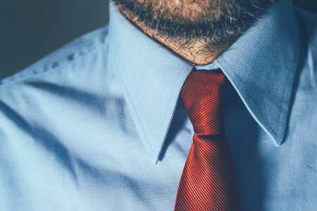 uncertain: Businessman in blue shirt and red necktie in office with strong shadows, suitable for intense business situation such as meeting or contract assignment with uncertain outcome, selective focus.