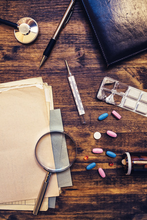 practitioner: Assorted office supplies on doctors desk. General medical practitioner workspace, top view.