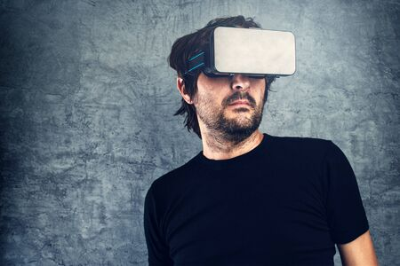 futuristic man: Adult Man wearing virtual reality goggles for 3d VR multimedia content, modern futuristic technology gadget