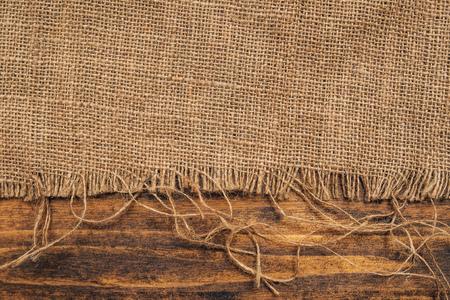 Burlap hessian sacking on wooden background, rustic backdrop