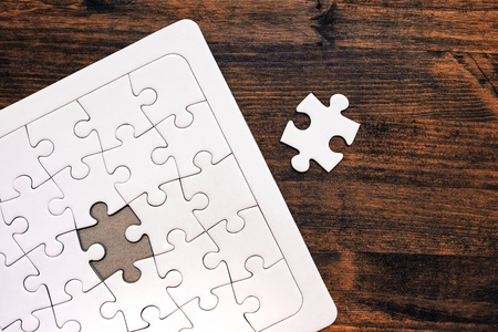 complete solution: Jigsaw puzzle with one missing piece left to complete, copy space, top view Stock Photo