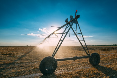 Automated agricultural center pivot irrigation system with drop sprinklers in harvested wheat stubble field in late summer afternoon, retro toned Stock Photo