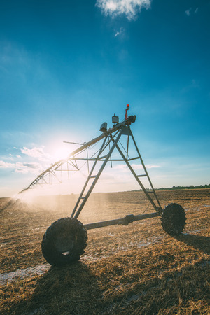 late summer: Automated agricultural center pivot irrigation system with drop sprinklers in harvested wheat stubble field in late summer afternoon, retro toned Stock Photo