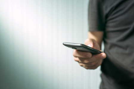 mobile telephone: Casual man using smart phone to send text message, male hands holding mobile telephone device, selective focus