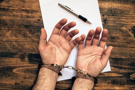 cuffed: Male hands cuffed, top view of police investigator detective desk with pencil and blank paper for statement Stock Photo