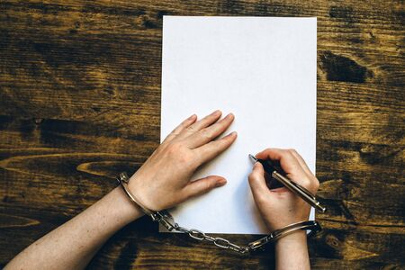 cuffed: Female hands cuffed signing confession, top view of police investigator detective desk Stock Photo