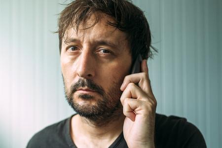 wearied: Tired adult man talking on mobile phone, studio indoors portrait