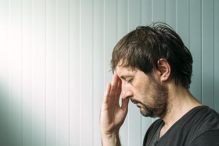 miserable: Profile portrait od miserable troubled man with serious expression, depressive male with hand on face.